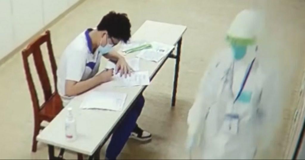 Estudiante chino presentando el Gaokao dentro de un pabellón aislado.